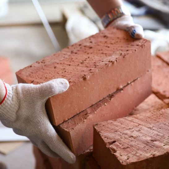 Photo is of a bricklayer carrying bricks in Newcastle